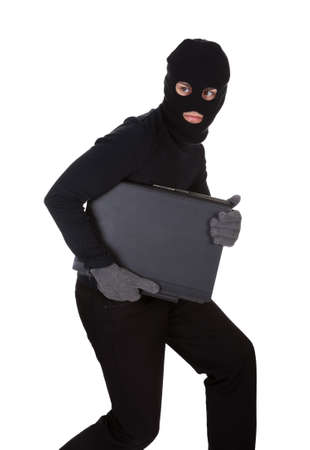 furtive: Thief dressed in black and wearing a balaclava stealing a laptop computer and making a furtive escape isolated on white Stock Photo