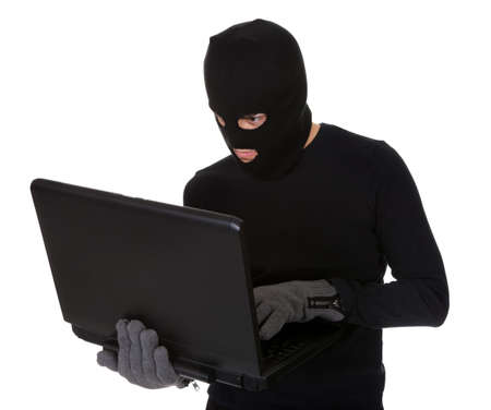 larceny: Thief in disguise stealing data from computer Stock Photo
