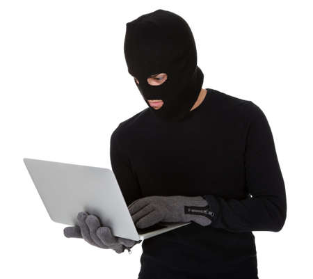 Thief in disguise stealing data from computer Stock Photo - 17384566