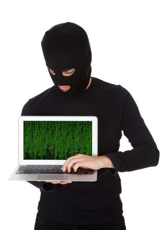 coder: Hacker dressed in black with a mask standing stealing data from a laptop with the screen pointed towards the camera in a breach of security