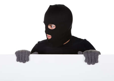 Thief in a balaclava and gloves looking around the edge of a blank sign with copyspace for your text isolated on white Stock Photo - 17384582