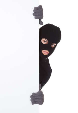 housebreaking: Thief in a balaclava and gloves looking around the edge of a blank sign with copyspace for your text isolated on white