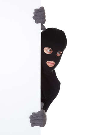 furtive: Thief in a balaclava and gloves looking around the edge of a blank sign with copyspace for your text isolated on white