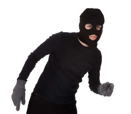 Thief wearing a balaclava dressed in blacked moving stealthily. Isolated on white Stock Photo - 17384665