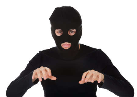 Thief wearing a balaclava dressed in blacked moving stealthily. Isolated on white Stock Photo - 17384639