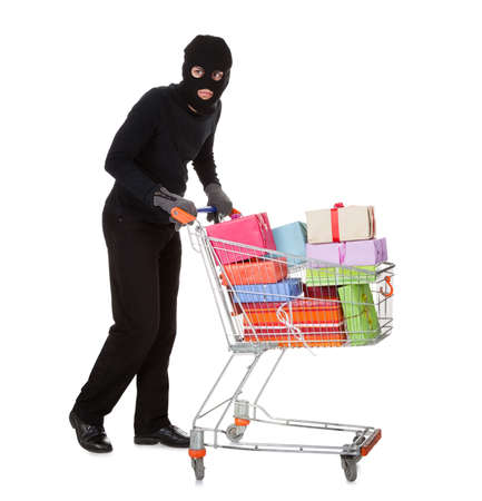larceny: Thief in a black costume and balaclava pushing a shopping trolley full of gifts and presents from a celebration isolated on white
