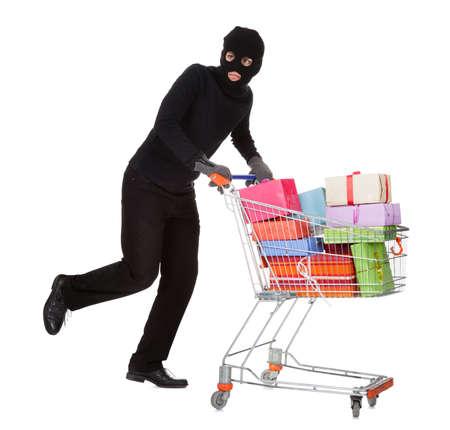 Dieb im schwarzen Kostüm und Sturmhaube schiebt einen Einkaufswagen voller Geschenke und Geschenke von einer Feier isoliert auf weiß Standard-Bild
