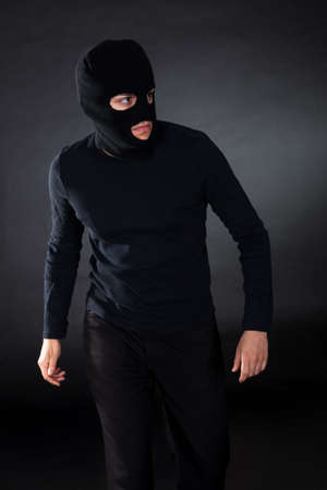 Thief wearing a balaclava dressed in blacked moving stealthily through the darkness as he prepares to commit robbery Stock Photo - 17384517