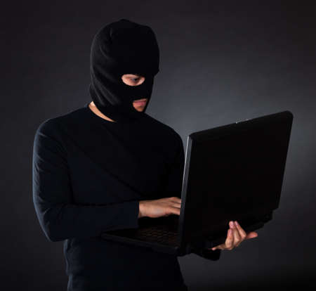furtive: Hacker in disguise stealing data from Computer Stock Photo