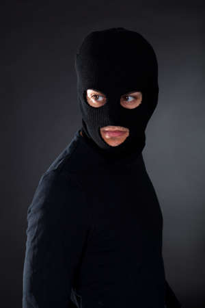 Thief wearing a balaclava dressed in blacked moving stealthily through the darkness as he prepares to commit robbery Stock Photo - 17384485