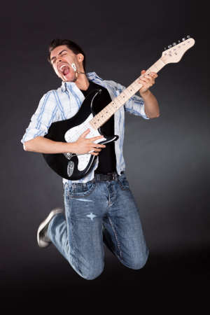 air guitar: Young musician jumping with his guitar while singing