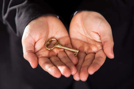 Conceptual closeup cropped image of an old-fashioned brass key held in outstretched cupped male hands photo