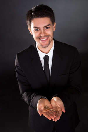 Smiling young businessman holding up a golden key in his hand photo