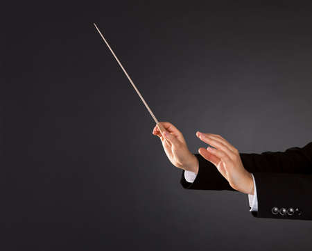 Closeup of the hands of a music conductor with a baton against a dark studio background with copyspace Stock Photo - 17389790