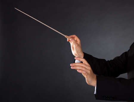 choral: Closeup of the hands of a music conductor with a baton against a dark studio background with copyspace