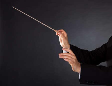 chóralne: Closeup z rąk dyrygenta muzyki pałką na ciemnym tle studio z copyspace