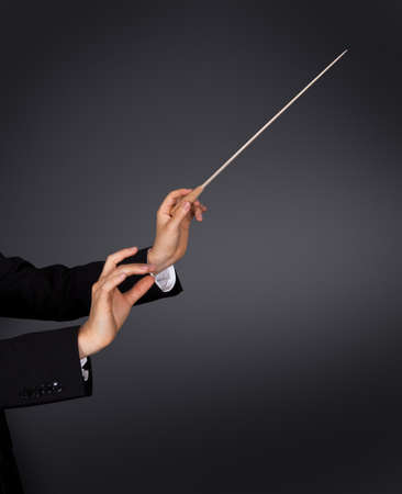 orchestra: Closeup of the hands of a music conductor with a baton against a dark studio background with copyspace