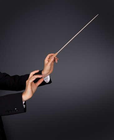orquesta clasica: Primer plano de las manos de un conductor de la música con un bastón contra un fondo oscuro estudio con copyspace Foto de archivo