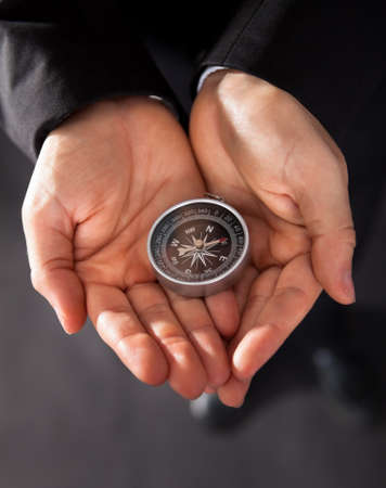 Businessman looking at a compass which he is holding in his hand with focus to the compass photo