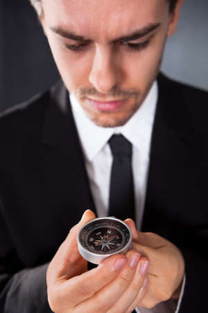 Businessman looking at a compass which he is holding in his hand with focus to the compass Stock Photo - 17384562
