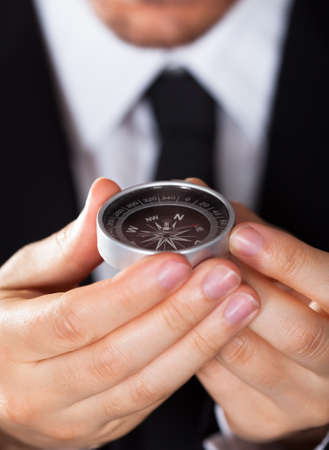 Businessman looking at a compass which he is holding in his hand with focus to the compass Stock Photo - 17384552
