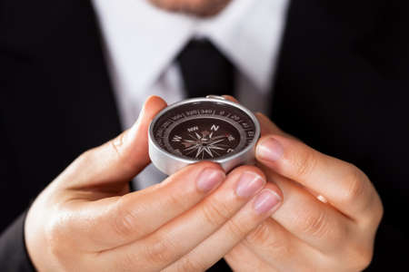 Businessman looking at a compass which he is holding in his hand with focus to the compass Stock Photo - 17384569