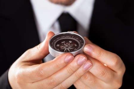Zakenman kijken naar een kompas dat hij in zijn hand die met de focus op het kompas Stockfoto