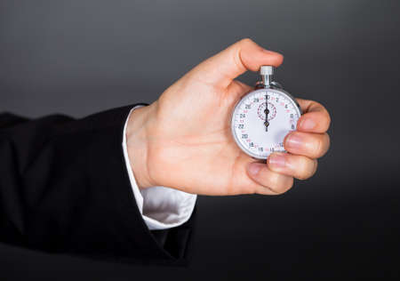 Business man holding stop watch in his hand photo