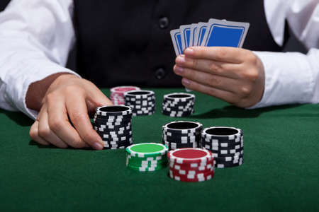 tokens: Male poker player about to place a bet moving a stack of tokens towards the centre of the gaming table with his free hand