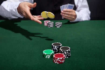 wager: Poker player increasing his stakes throwing tokens onto the gaming table to meet or beat his opponents wager to stay in the game