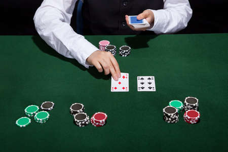 croupier: Croupier dealing cards in a poker game placing them face up on the green baize of the gaming table
