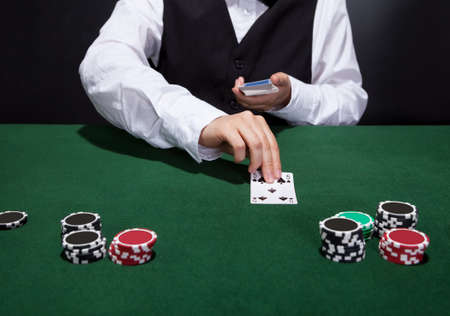 casino dealer: Croupier dealing cards in a poker game placing them face up on the green baize of the gaming table