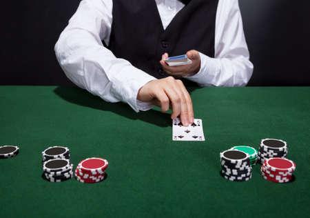 fichas casino: Croupier repartir las cartas en una partida de póquer colocándolos boca arriba sobre el tapete verde de la mesa de juego