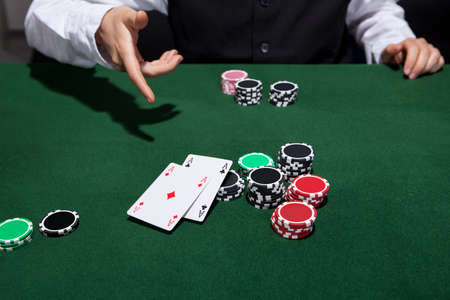 croupier: Poker player throwing down a pair of aces as he declares his hand and folds during a game of poker at a casino gaming table Stock Photo