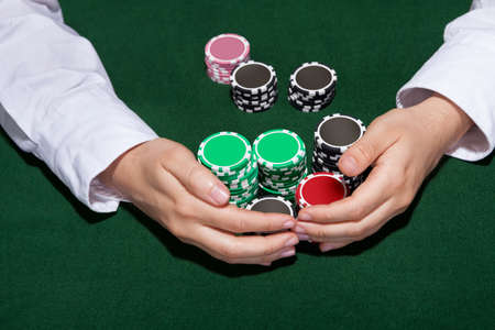 croupier: Croupier collecting in the bets at a casino table with his hands encircling various stacks of tokens or chips Stock Photo