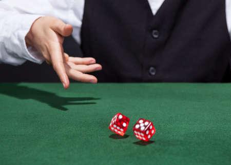 dados: Croupier lanzar un par de dados rojos en todo el fieltro verde sobre una mesa de juego en un casino en un juego de azar