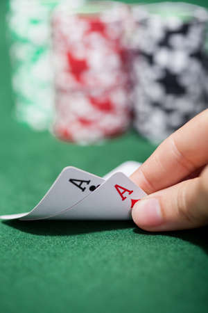 card game: Hand of a male poker player lifting the corners of two cards on the green felt checking a pair of aces