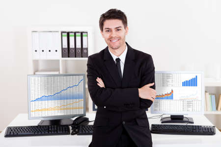 Confident smiling stock broker sitting on the edge of his desk surrounded by graphs and analytics indicating a successful bull market Stock Photo - 17384559