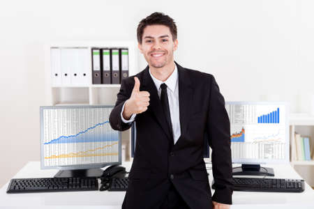 trading board: Confident smiling stock broker sitting on the edge of his desk surrounded by graphs and analytics indicating a successful bull market