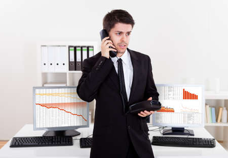 Worried stock broker talking on the phone backed by graphs depicting a crisis and a bear market with huge losses in the market Stock Photo - 17384547