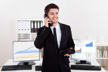 agente comercial: Entusiasta joven stock corredor masculino en un mercado alcista que sostiene un teléfono