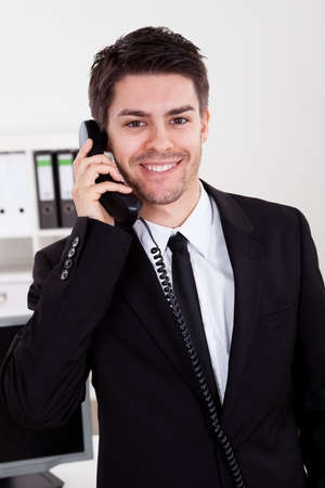 Enthusiastic young male stock broker in a bull market holding a telephone Stock Photo - 17384589