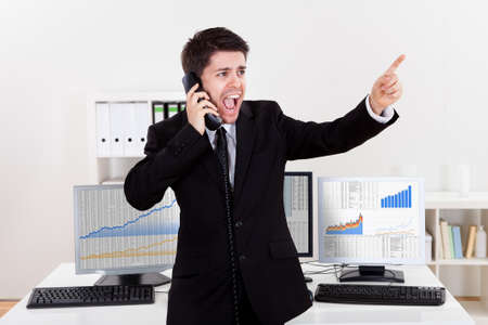 Enthusiastic young male stock broker in a bull market holding a telephone and yelling out a buy or sell order on stocks or bonds Stock Photo - 17384556