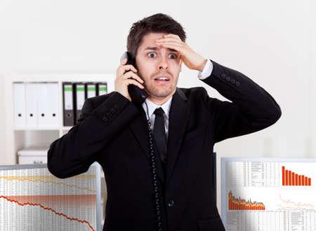 agente comercial: Preocupado corredor de bolsa habla por tel�fono respaldado por gr�ficos que representan una crisis y un mercado a la baja, con p�rdidas enormes en el mercado Foto de archivo