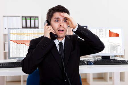 agente comercial: Preocupado corredor de bolsa habla por teléfono respaldado por gráficos que representan una crisis y un mercado a la baja, con pérdidas enormes en el mercado Foto de archivo