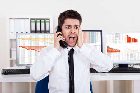 negative equity: Worried stock broker talking on the phone backed by graphs depicting a crisis and a bear market with huge losses in the market Stock Photo