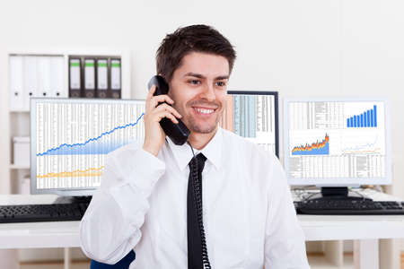 wall street: Enthusiastic young male stock broker in a bull market holding a telephone