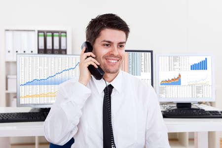bolsa de valores: Entusiasta joven stock corredor masculino en un mercado alcista que sostiene un tel�fono