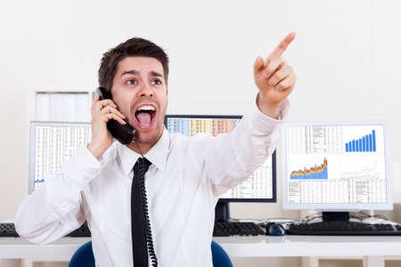 agente comercial: Entusiasta joven stock corredor masculino en un mercado alcista que sostiene un teléfono y gritar una orden de compra o venta de acciones o bonos Foto de archivo