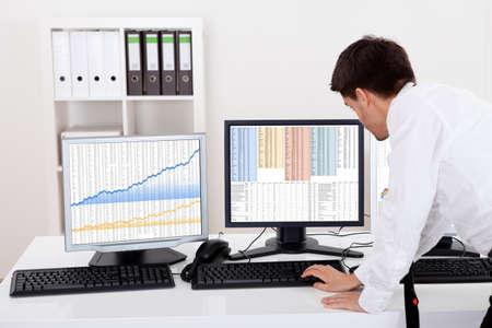 �quit�: Au cours de l'�paule vue des �crans d'ordinateur d'un courtier en valeurs mobili�res n�gociation dans un march� haussier montrant des graphiques ascendants Banque d'images